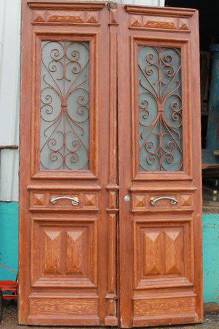 These natural wood grain set of entry doors with decorative iron work are made from white pine. They are From North Africa and measure 27