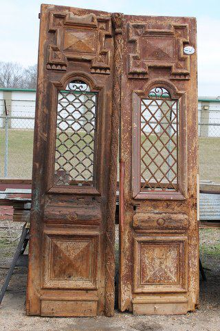 These doors with decorative iron work are made from white pine and hail from North Africa. Dimensions: 28